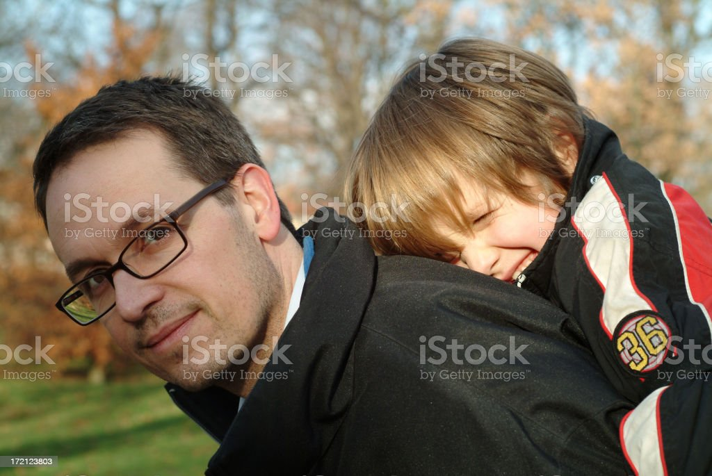 Father with son on his back outdoors royalty-free stock photo