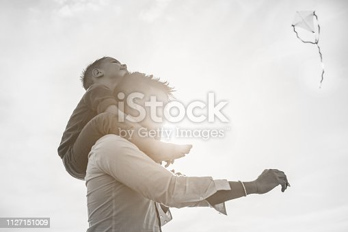 Father with son on shoulder flying with kite and having fun on the beach - Dad enjoying time with his child - Love, freedom and family concept - Soft focus on kid face - Black and white editing