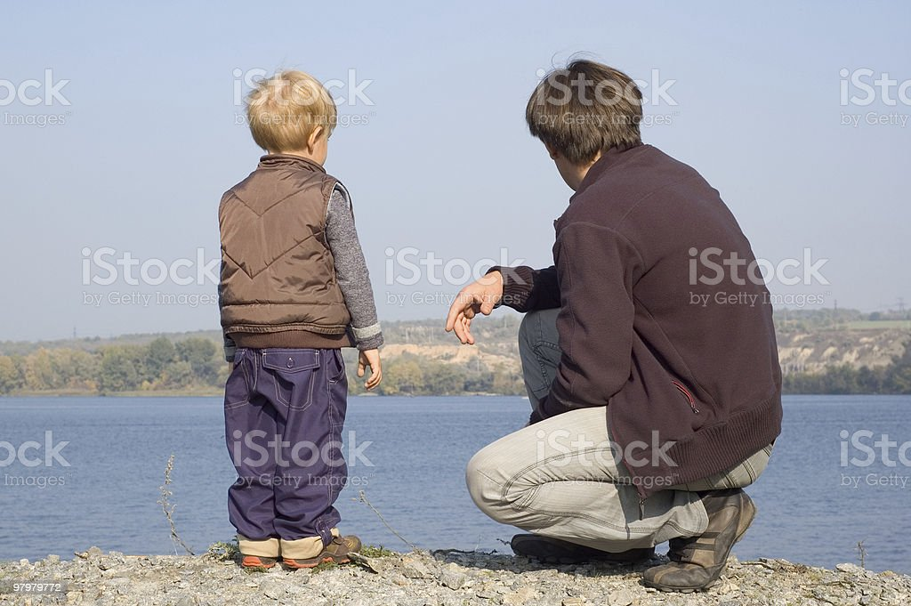 father with son on the river bank royalty-free stock photo