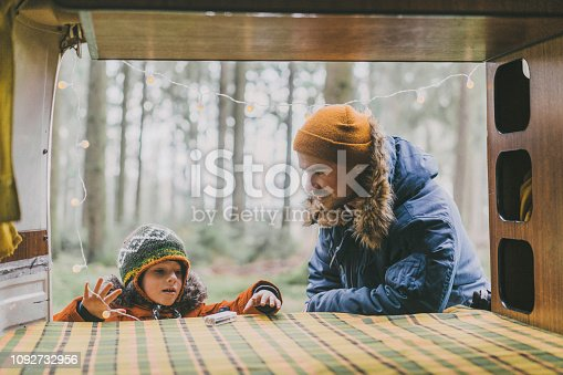 Caucasian father with son placing lights in camper van