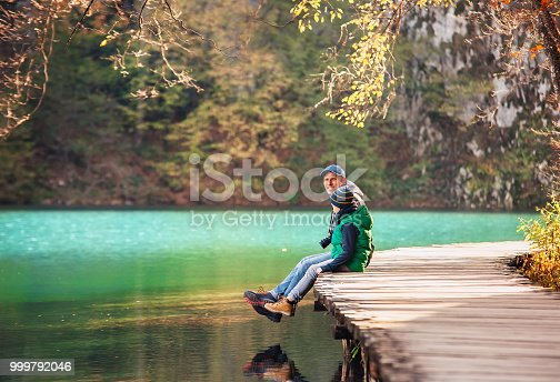 Father with son sit on bridge near the mountain lake, Nature national park in Croatia, Plitvice Lakes