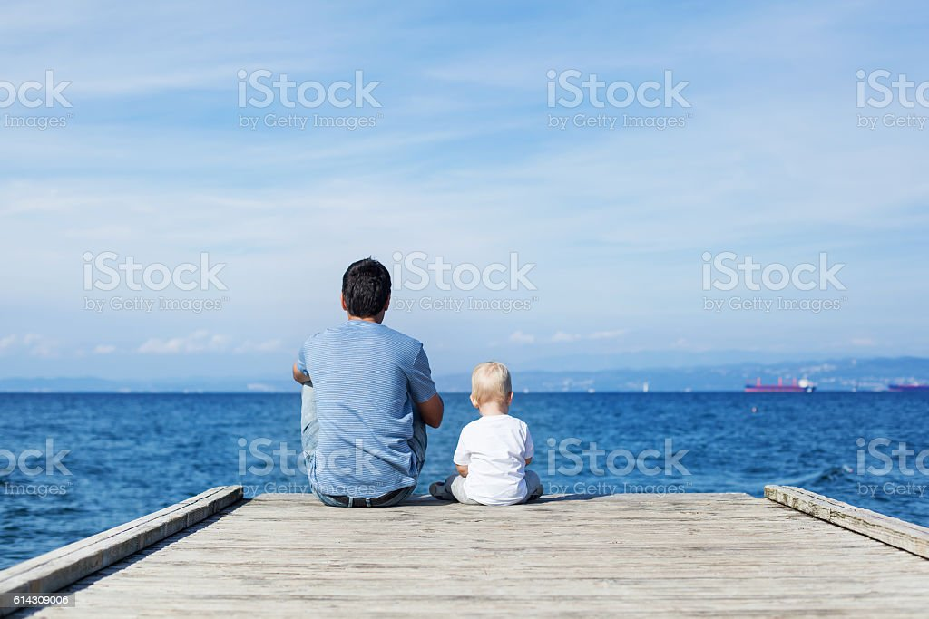 Father with son sitting on the sea pier stock photo
