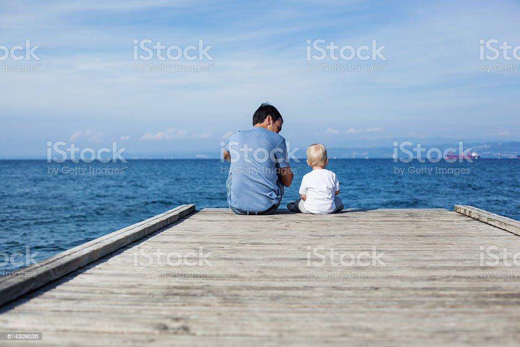 Pai com o filho sentado no cais do mar - foto de acervo