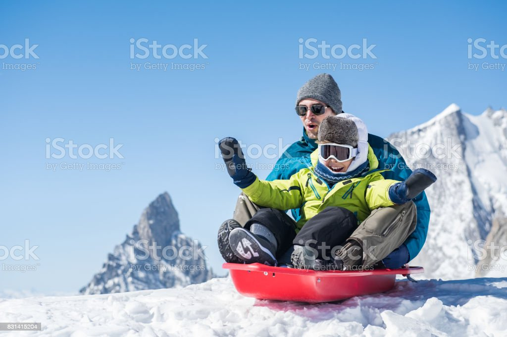 Father with son sledding stock photo