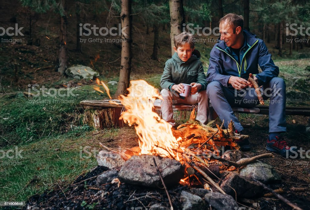Father with son warm near campfire, drink tea and have conversation royalty-free stock photo