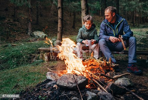istock Father with son warm near campfire, drink tea and have conversation 674906646