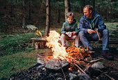 暖かいキャンプファイヤーの近くの息子と父親、お茶を飲むし、会話