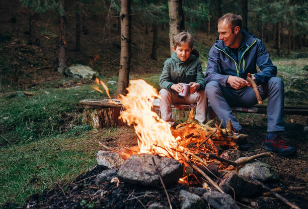 Father with son warm near campfire, drink tea and have conversation stock photo
