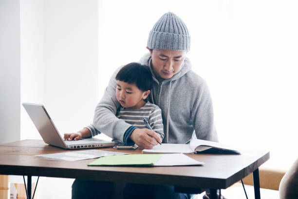 Father with son working at home Japanese man in casual clothes writing a document and his son using a laptop on the desk. He's working and doing childcare at home. stay at home father stock pictures, royalty-free photos & images