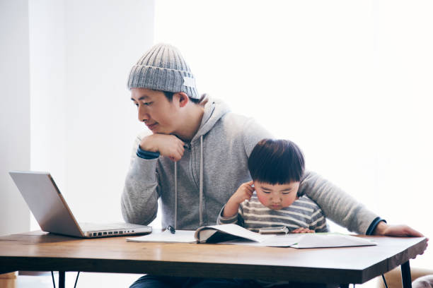 Father with son working at home Japanese man in casual clothes using a laptop and his son using a smartphone on the desk. He's working and doing childcare at home. stay at home father stock pictures, royalty-free photos & images