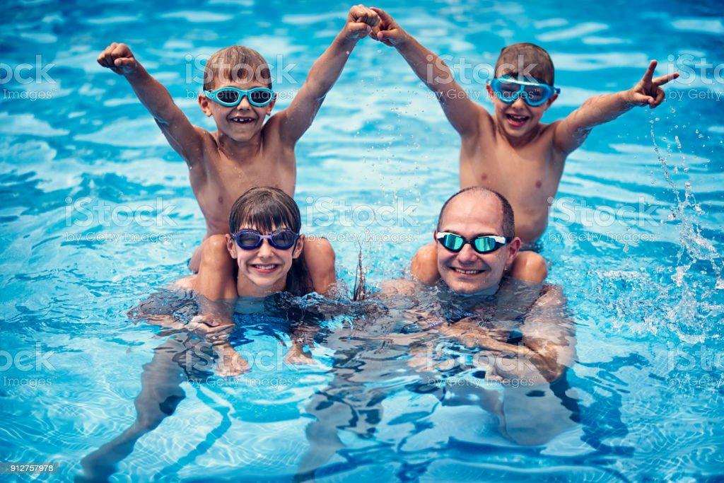 Vater mit drei Kdis spielen in Resort Pool. – Foto
