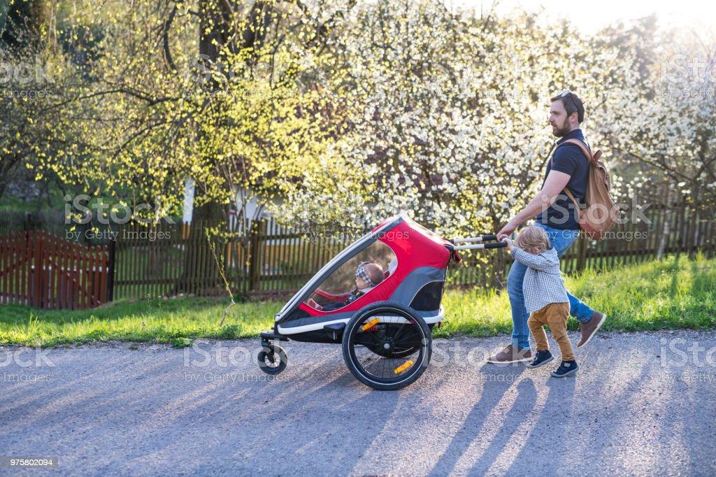 Ein Vater mit Kleinkind Sohn Frühling Natur ein Jogger außerhalb einschieben. - Lizenzfrei Alleinerzieher Stock-Foto