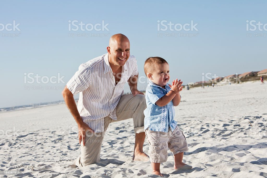 Father with toddler walk on beach royalty-free stock photo