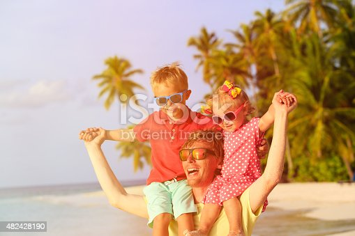 505122600 istock photo father with two kids on shoulders having fun at beach 482428190