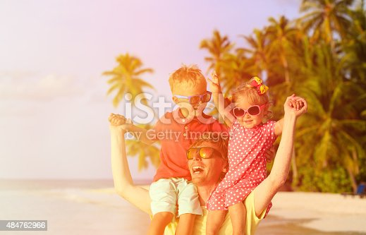 505122600 istock photo father with two kids on shoulders having fun at beach 484762966