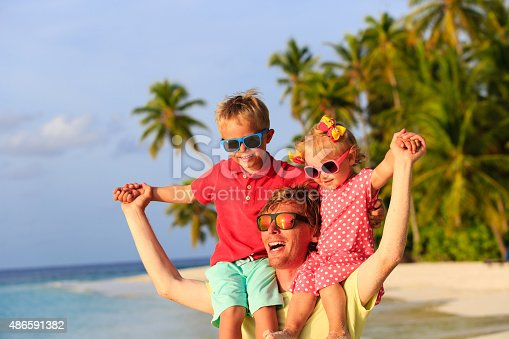 505122600 istock photo father with two kids on shoulders having fun at beach 486591382