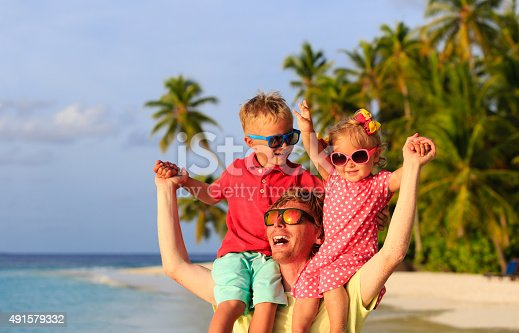 505122600 istock photo father with two kids on shoulders having fun at beach 491579332