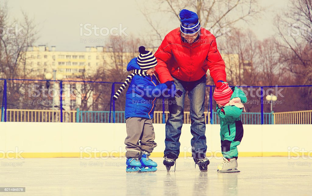 father with two kids skating, family winter sport foto stock royalty-free