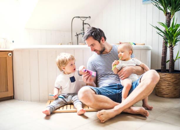 far med två småbarn tandborstning i badrummet hemma. - baby bathtub bildbanksfoton och bilder