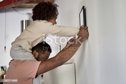 Side view of Afro-Caribbean man in late 20s with 3 year old daughter on his shoulders as they find a place to hang picture in new apartment.