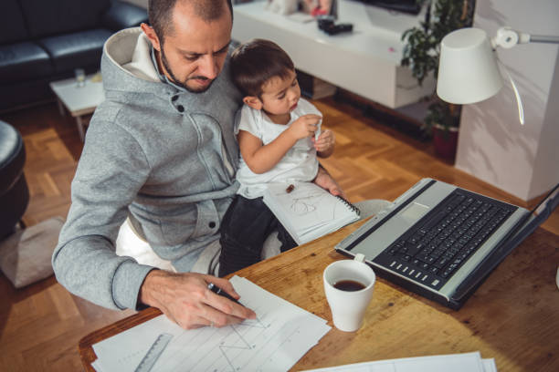 Father working at home and holding son on his lap stock photo