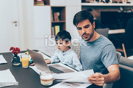 Handsome father working with documents and laptop at home with his little son