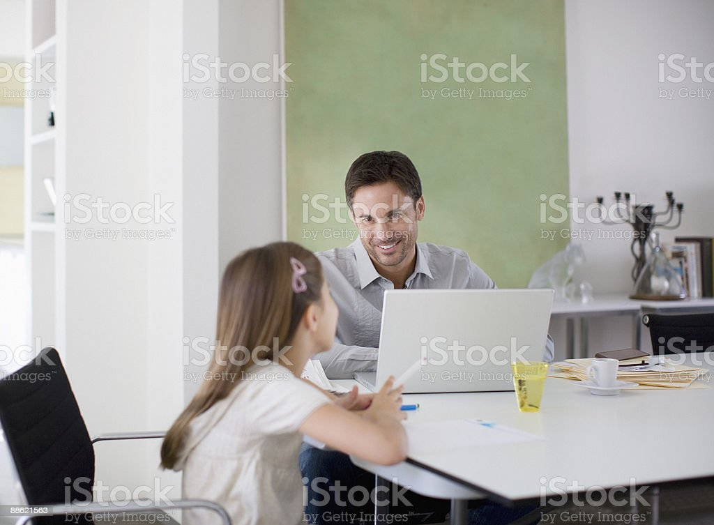 Father working at table while daughter draws royalty-free stock photo