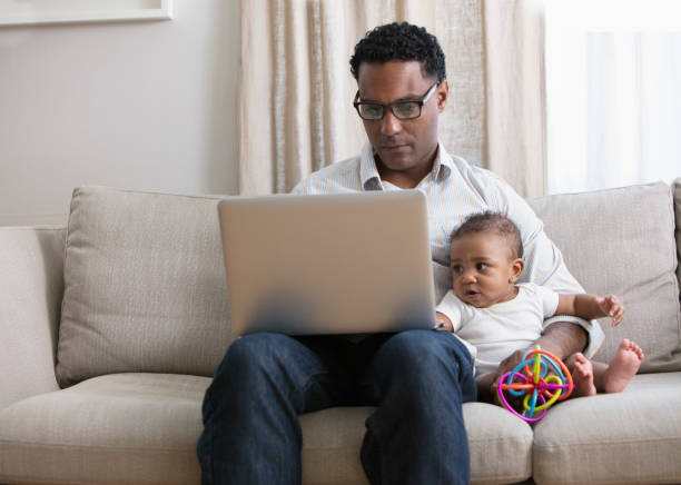 Father working from home and taking care of baby daughter
