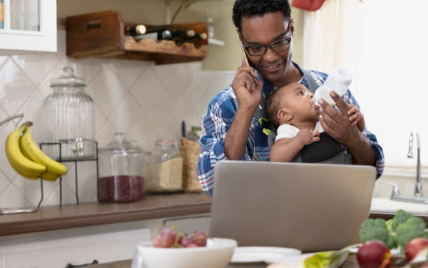 Father working from home holding baby