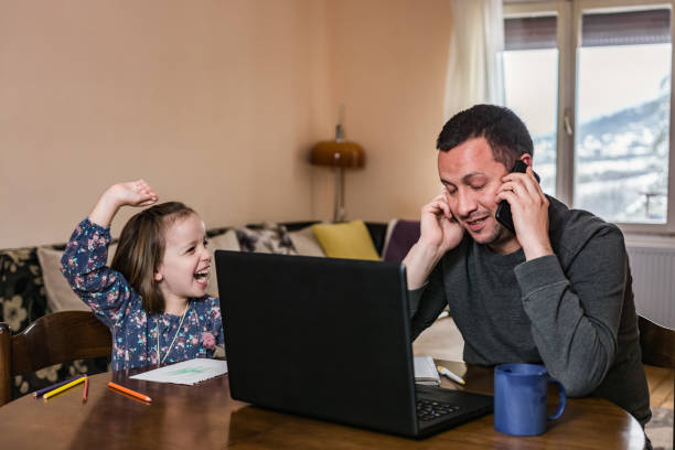 Father working from home with young child in quarantine isolation stock photo