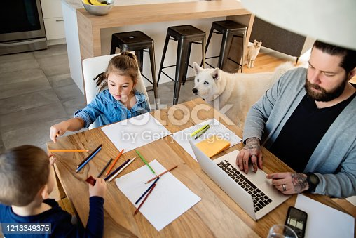 Millennial generation father working from home with small children while in quarantine isolation during the Covid-19 health crisis. Little boy is two, little girl is four. Father has tattoos and a beard. The family cat and dog passing in background. Horizontal indoors waist up shot with copy space.