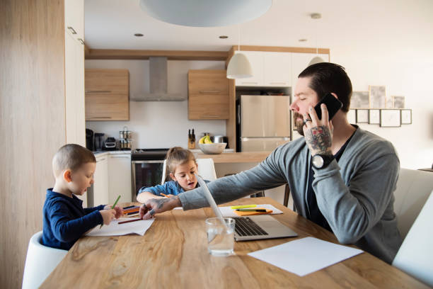Father working from home with young children in quarantine isolation Covid-19 stock photo