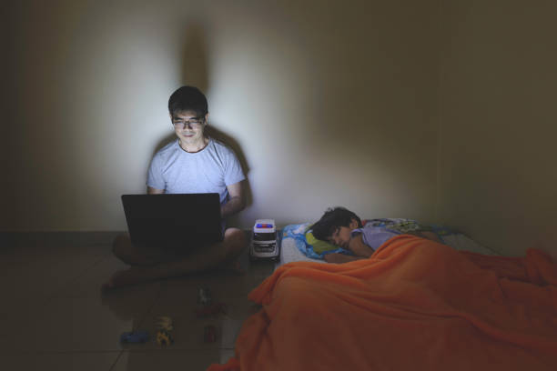 Father working on laptop at night next to his kid sleeping stock photo