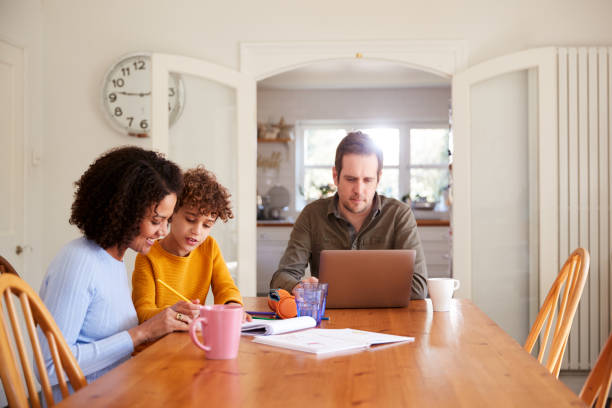 Vater arbeitet am Laptop als Mutter hilft Sohn mit Hausaufgaben am Küchentisch – Foto