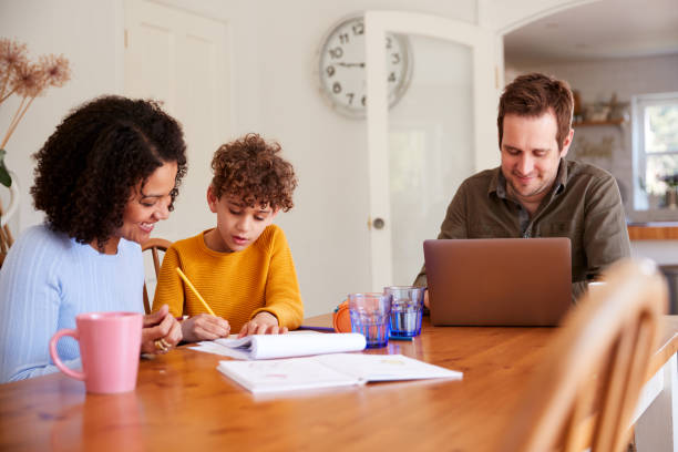 father works on laptop as mother helps son with homework on kitchen table - work from home stock pictures, royalty-free photos & images