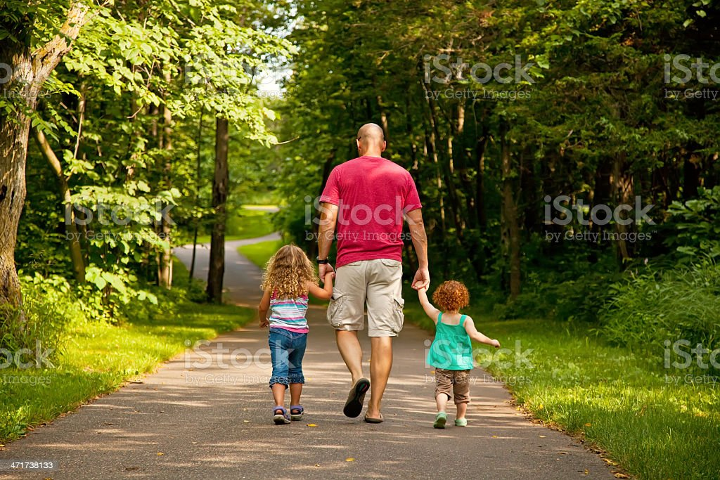 Father & Young Daughters Walking in Park stock photo
