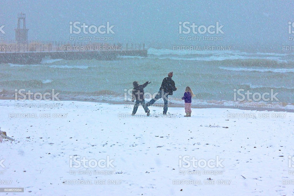 Father, young son and daughter throwing snowballs at beach stock photo