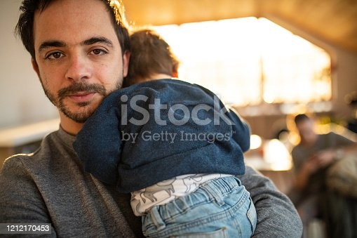 Adult man Holding baby boy indoors,looking at camera
