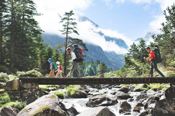 Fathers and children hiking together in mountains stock photo