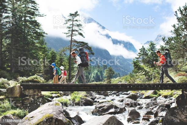 Photo of Fathers and children hiking together in mountains