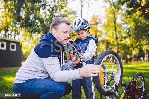 Father's day Caucasian dad and 5 year old son in the backyard near the house on the green grass on the lawn repairing a bicycle, pumping a bicycle wheel. Dad teaches how to repair a child's bike.
