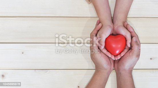 istock Father's day celebration, I love you dad, parenting concept with daddy and child's hand holding heart young kid's hands supporting red heart, csr charity donation, adoption family health nursing care 1045695978