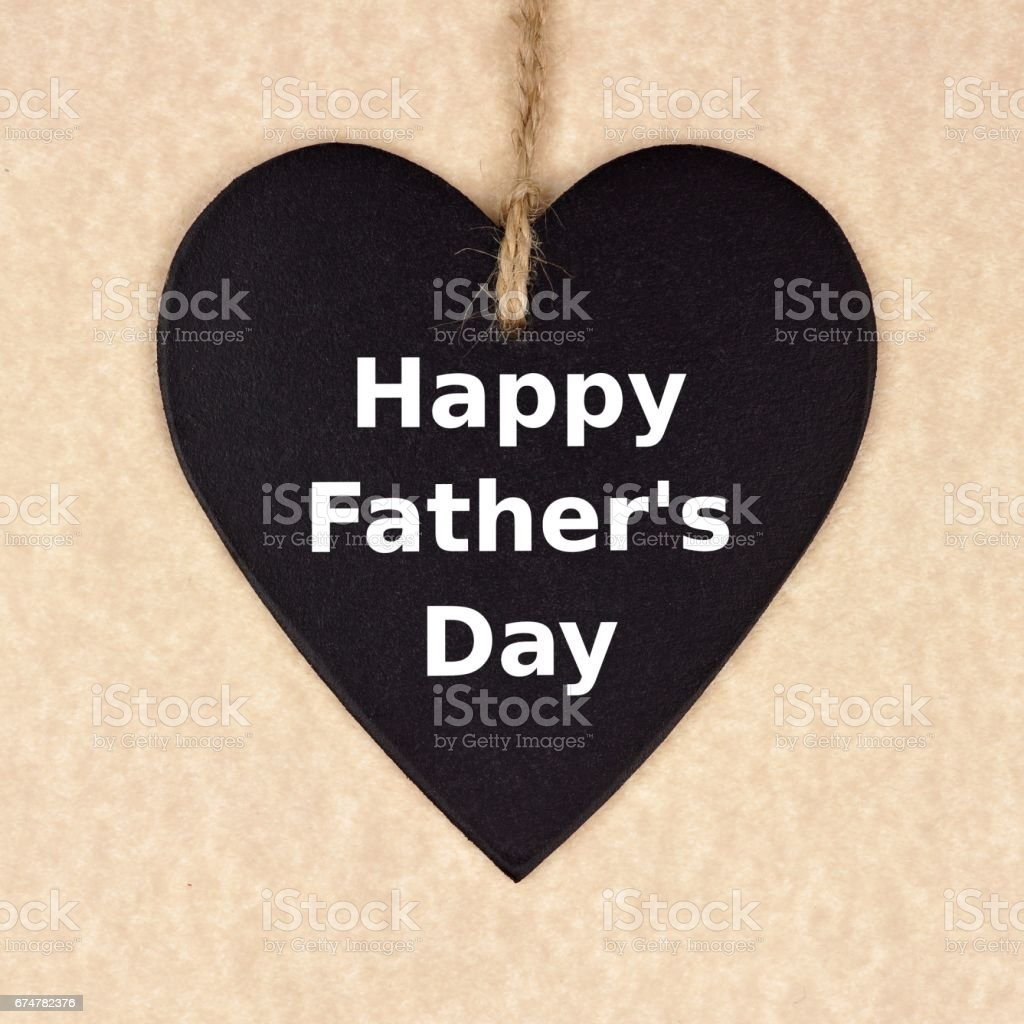 Fathers Day chalkboard heart over brown paper stock photo