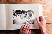 Fathers day composition. Hands of unrecognizable man holding a photo album, black-and-white pictures. Studio shot on wooden background.