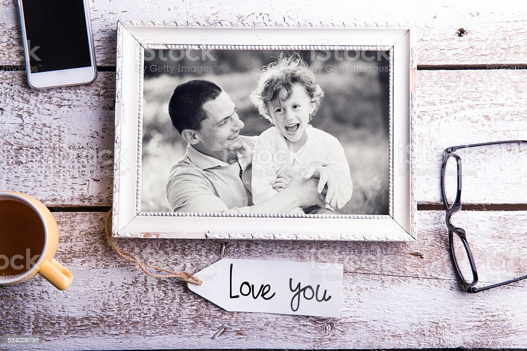 Fathers day composition. Picture of father with son in frame stock photo