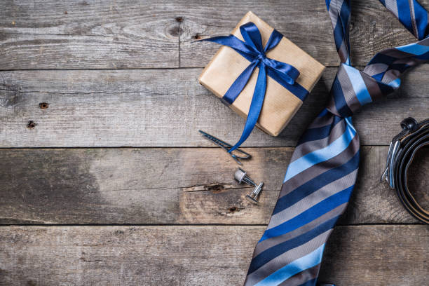 father's day concept - present, tie on rustic wood background - fathers day stock photos and pictures