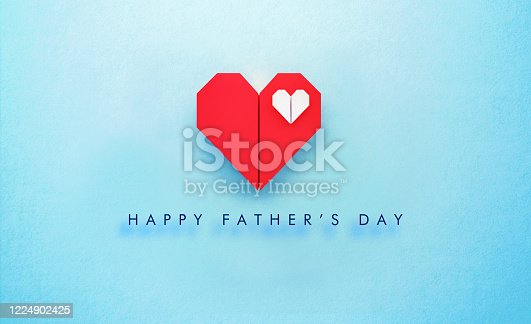 White origami heart sitting inside of a red origami heart on turquoise background.  Happy Father's Day written below the heart. Horizontal composition with copy space. Father's Day concept.