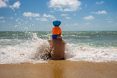 father's day. dad with a baby on his shoulders playing in the spray of sea foam. safe parent concept.