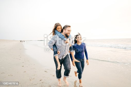 Dad spending time on the beach with his daughters