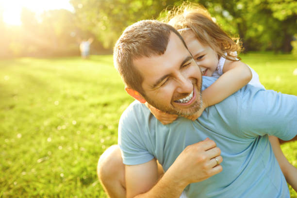 Father's day. Father plays with his daughter in the summer park. stock photo